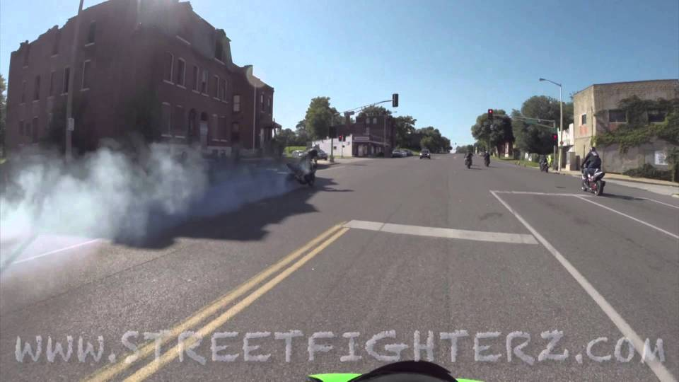 Motorcycles do burnouts in oncoming traffic through cars.