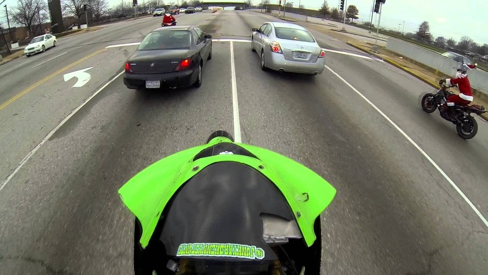 Motorcycle splits cars in a wheelie while running red light